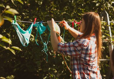 beautiful woman drying swimsuits on clothesline