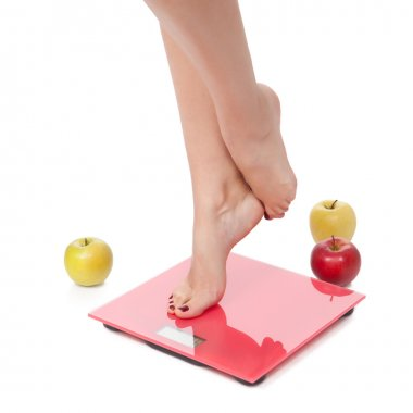 Woman perfect shaped legs on scale with apple