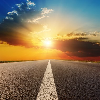 asphalt road under sunset with clouds