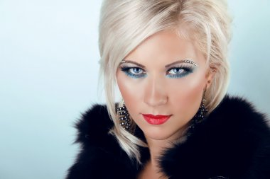 Fashion blond woman with blue eyes and red lips, wearing in fur
