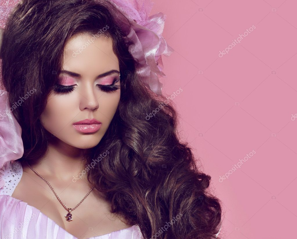 Beautiful young girl with curly hair and bright make-up. Jewelry