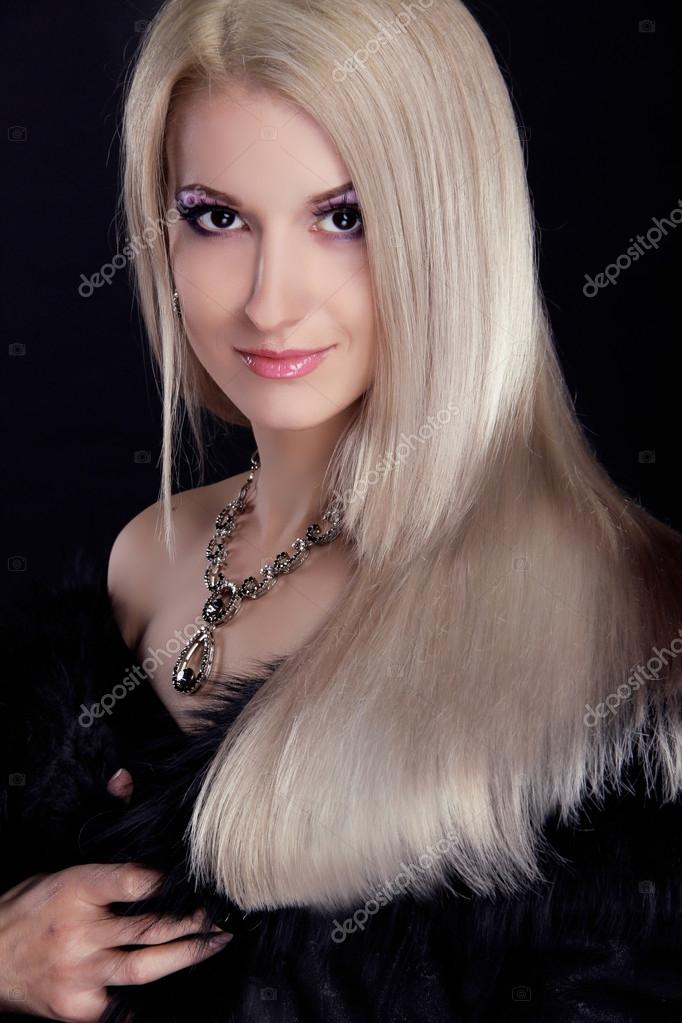 Blond woman with Healthy Long Hair isolated on black background