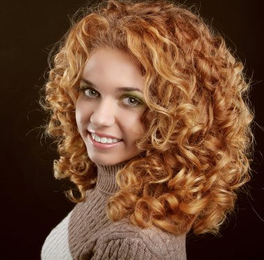 Healthy Curly Hair. Attractive smiling woman portrait on black b