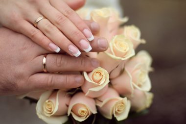Wedding rings and Hands on roses bouquet