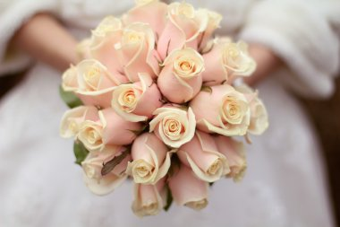 Wedding bouquet of roses in hands of the bride
