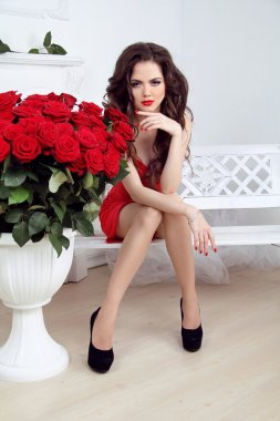 Beautiful sexy woman with flowers bouquet of red roses at interi
