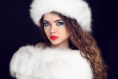 Beautiful Girl wearing in White Fur Coat and Furry Hat. Winter W