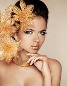 krásná dívka se zlatými květy. krása modelu ženská tvář. za
