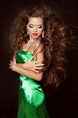 Krásná mladá žena s dlouhými kudrnatými vlasy v elegantní šaty pos