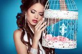 Fotografia ragazza romantica appoggiata su gabbie per uccelli depoca con ornamen