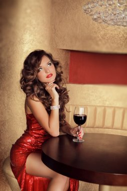 Beautiful girl in red dress sitting at the table holding vine g
