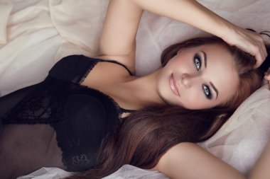 Fashion portrait of beautiful brunette woman on bed