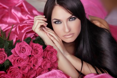Beauty portrait of brunette girl with pink Roses lying on the be