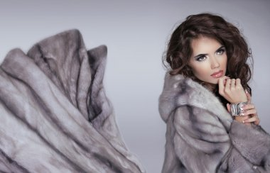 Mink fur coat. Winter girl. Beautiful brunette woman isolated on