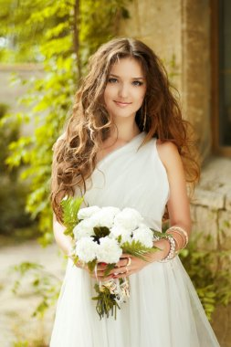 Beautiful young bride with wedding makeup and long wavy hair sty