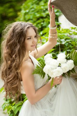 Beautiful happy bride with  long wavy hair and wedding makeup ho