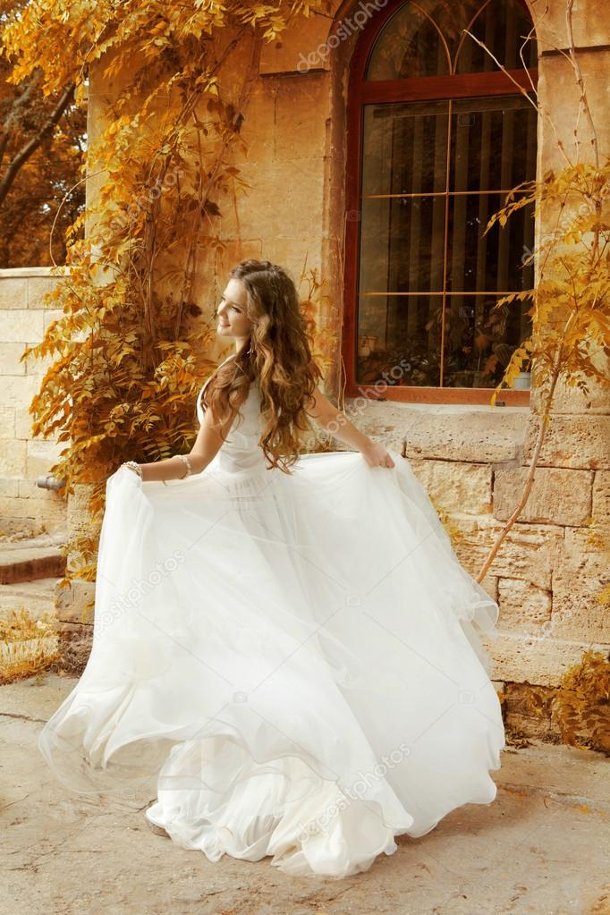 Beautiful bride woman in white wedding dress running at autumn p