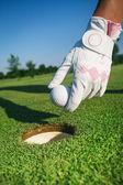 Close-up ruka drží golfový míček