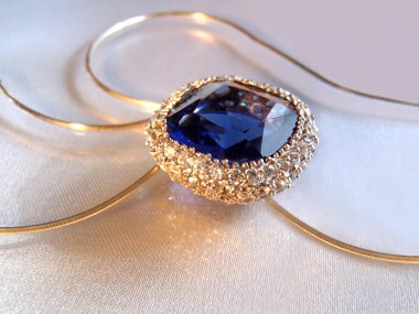 Silver pendent with sapphire and cubic zirconias on a chain, macro.