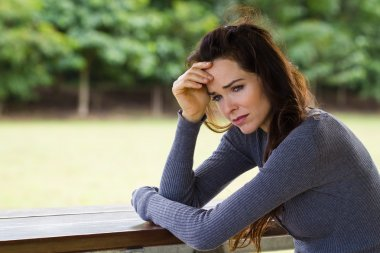 Sad and worried woman sitting outdoors