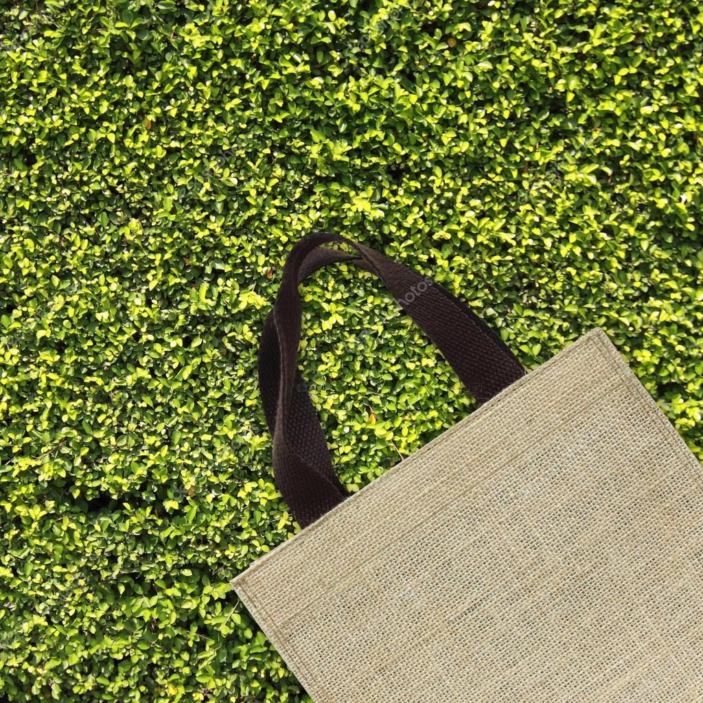 Shopping bag on green leaves