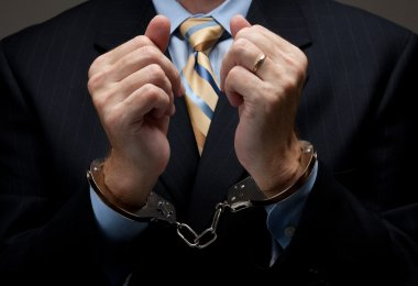 A man in a blue business suit holding hands in handcuffs in front of his chest stock vector
