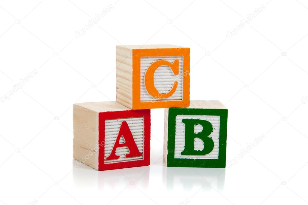 colored wooden letter blocks including red green and yellow on a white background with copy space photo by miflippo
