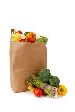 Brown grocery sack full of vegetables on white