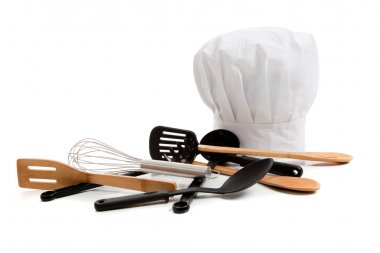Chef's toque with various cooking utensils on white