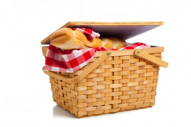 Wicker picnic basket with bread on white