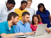 Různorodá skupina studentů/přátelé z koleje při pohledu na počítači