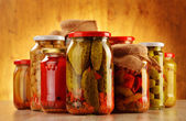 Photo Composition with jars of pickled vegetables. Marinated food