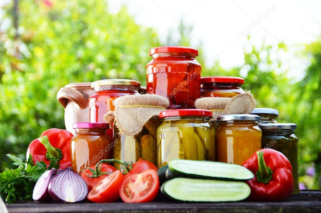 Jars of pickled vegetables in the garden. Marinated food