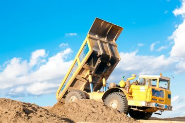 Heavy dump truck unloads soil on the sand
