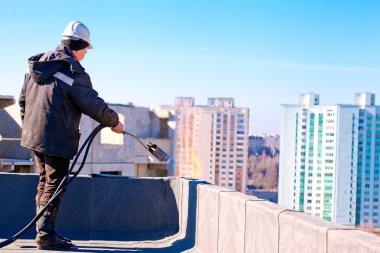 Roofer worker installing roofing felt