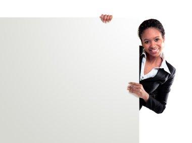 Female representative pointing towards placard and smiling at camera