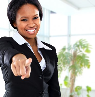 Smiling black business woman pointing on camera in office