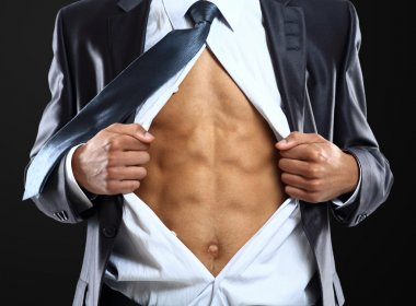 Business man tears open his shirt in a super hero fashion getting ready to save the day isolated over white background