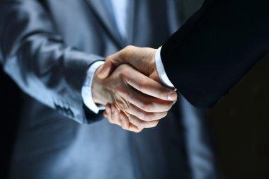 Handshake - Hand holding on black background stock vector