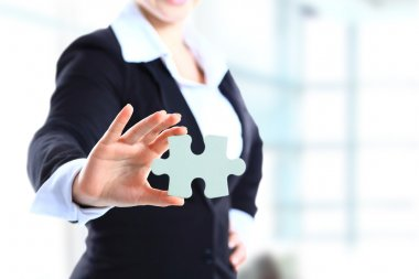 Business woman holding a piece of puzzle