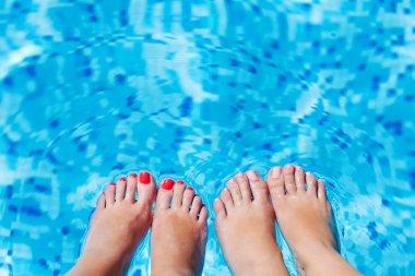 Women foot splashing in swimming pool