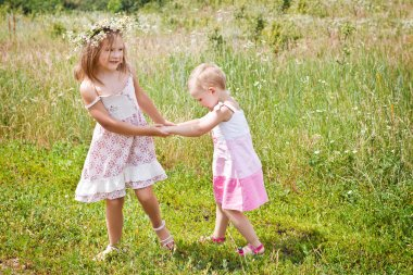 Little girls playing on a summer meadow
