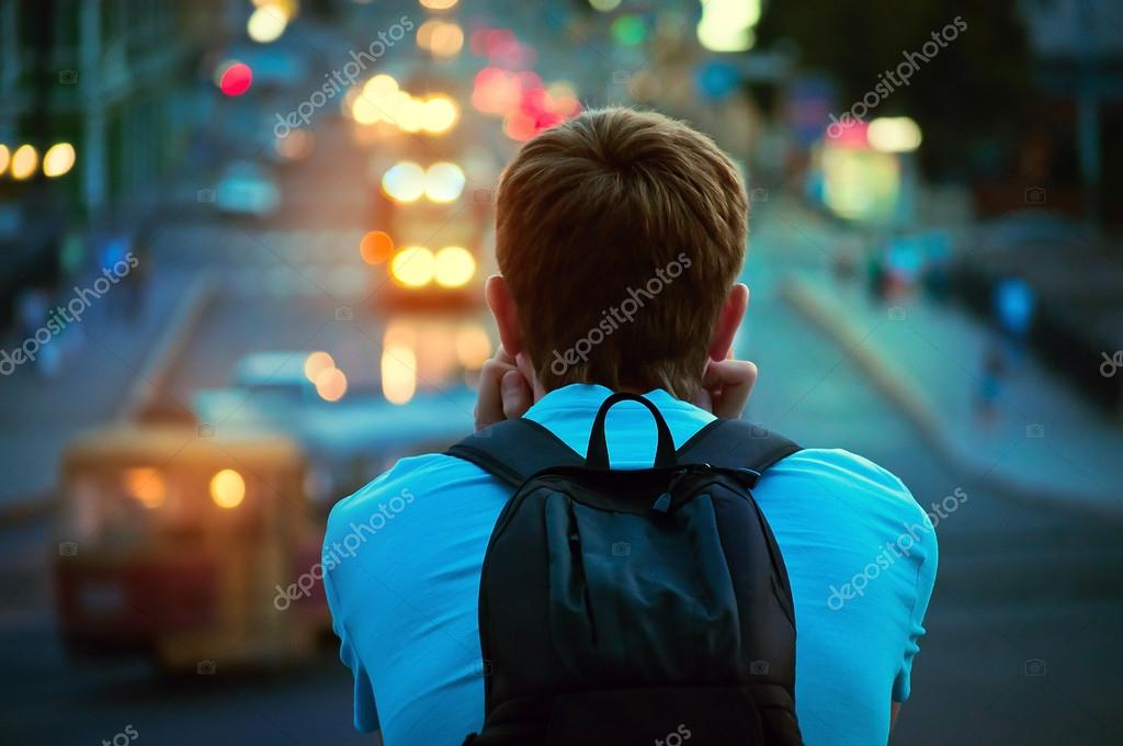 lonely guy sitting and looking at the lights of the evening city