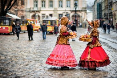 two woman in traditional clothes standing in the square in old city Lvov