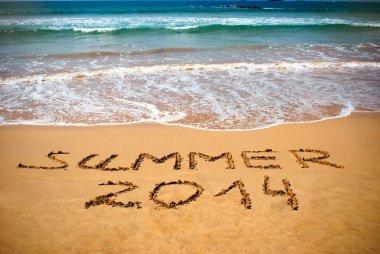 Inscription on wet sand Summer 2014. Concept of summer vacation