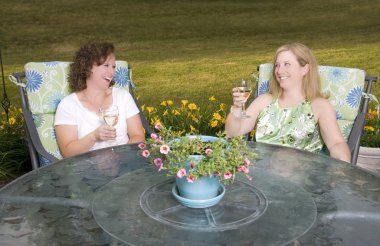 Women on Patio Laughing with Wine