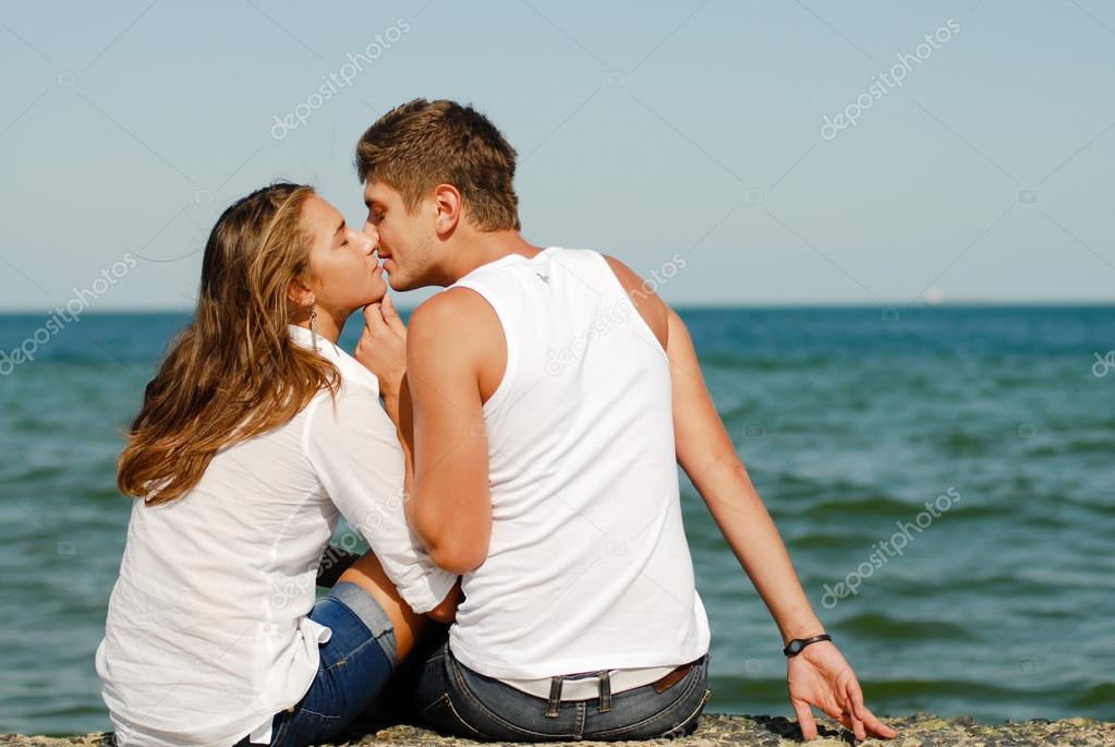 Happy young couple kissing by blue sea over blue sky background