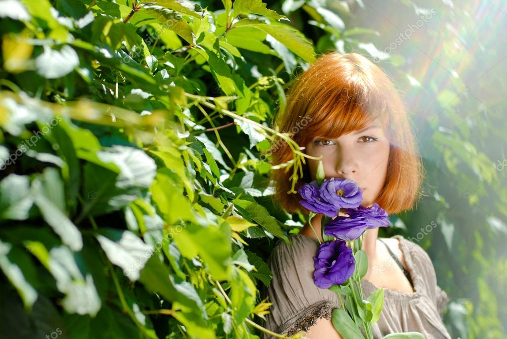 Pretty redhead teenage girl with purple rose by green leaves bac