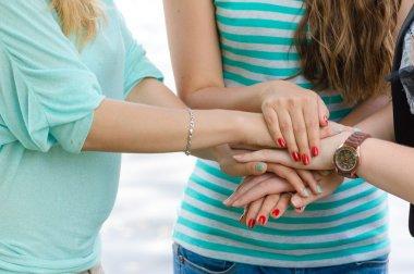 Three happy teenage friends holding hands like team