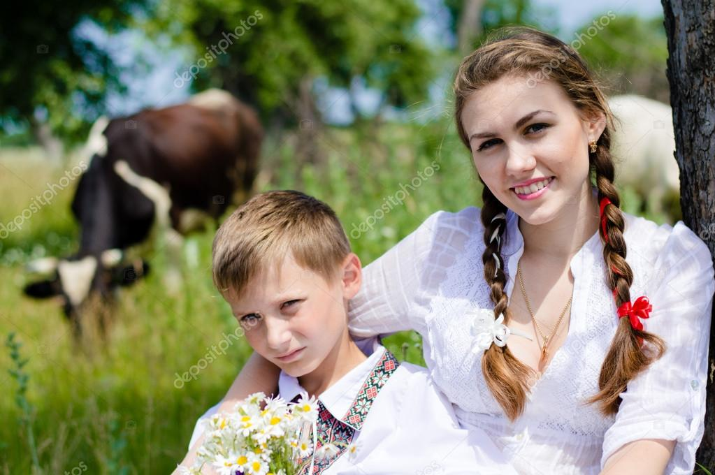 Teenage sister and little brother sitting by cow herd